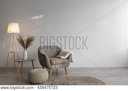 Retro Armchair With Plaid, Luminous Lamp, Dry Plants In Vase On Table, Ottoman And Round Carpet