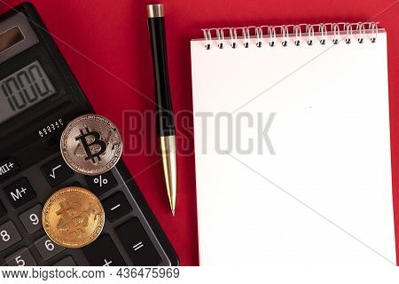 White Notepad With Calculator, Stylish Pen And Bitcoin Coins On A Red Background. Copy Space.