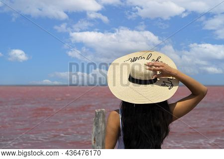 Woman Traveler In Hat Looks At Amazing Exotic Pink Salt Lake And Blue Sky. Wanderlust Travel Concept