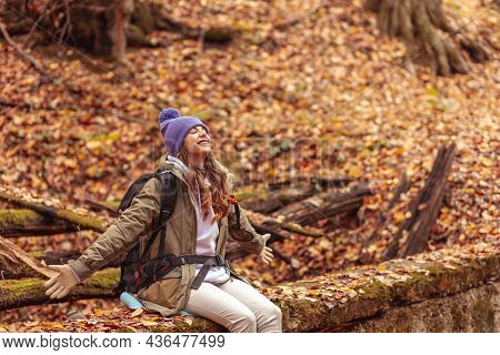 Beautiful Active Woman Relaxing Outdoors On A Sunny Autumn Day, Sitting In The Forest While Taking A