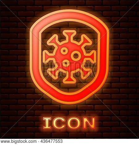 Glowing Neon Shield Protecting From Virus, Germs And Bacteria Icon Isolated On Brick Wall Background