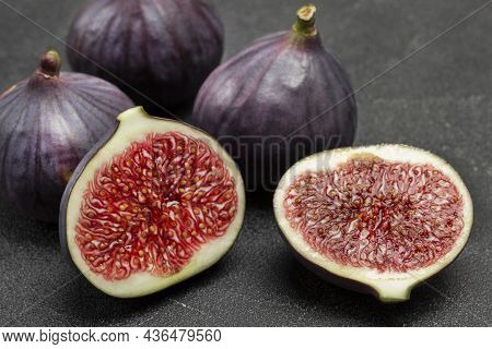 Two Halves Of Fig And Whole Purple Figs. Ripe Fruit Pulp. Close Up. Black Background.
