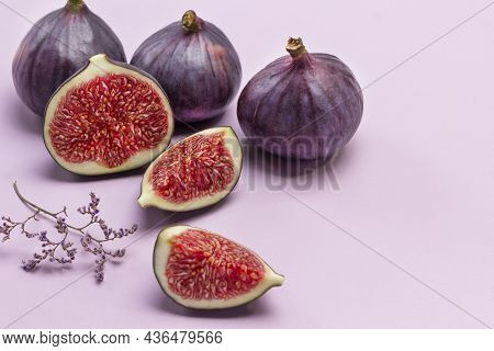 Whole Purple Figs And Fig Halves. Ripe Fruit Pulp. Copy Space. Pink Background.