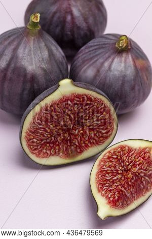 Two Halves Of Fig And Whole Purple Figs. Ripe Fruit Pulp. Close Up.