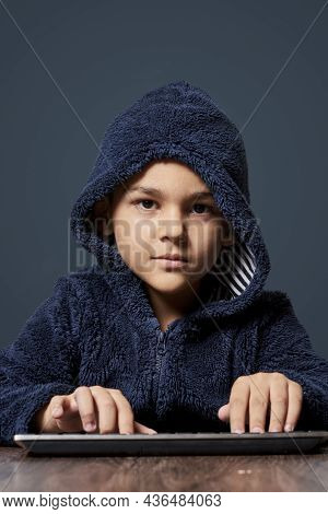 A Little Kid With A Hoodie Typing Computer Keyboard. Cute Multi-racial 8-years Old Boy Wearing Hoodi