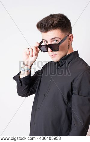 Portrait Of An Attractive Young Man Wearing Sunglasses. Studio Shot, Model Looking To The Camera. Wh