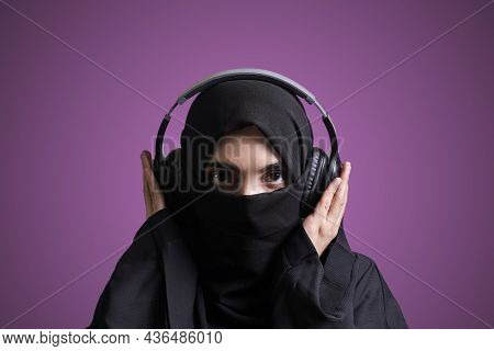 Muslim Woman In Hijab Listening To Music With Wireless Headset. Arabic Girl In Traditional Nikab Clo