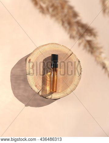 Glass Perfume Sample With Brown Liquid On A Wooden Tray Lying On A Beige Background With Pampas Gras