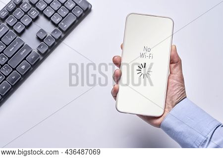 Lack Of Access To Internet. A Person Holds A Smartphone With No Wi-fi Inscription On Screen. Broken