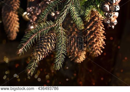 Christmas Card With A Spruce Branch With Big Cones And Toys From Pink Bells. Festive Background Of A