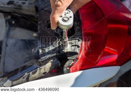 Motorcycle Repair And Maintenance. The Man Unscrews The Fasteners With A Socket Wrench.