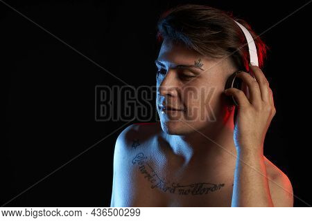 Portrait Latin Man With Headphones Listening To Music With Tattoo