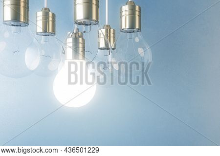 Glowing Light Bulb On Blurry Blue Wall Background. Idea, Innovation, Solution And Invention Concept.
