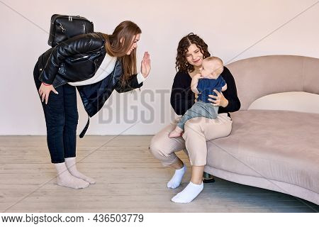 Young Mother Is Leaving Kid With Babysitter In Lounge.