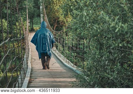 Girl With Backpack Under Blue Raincoat Is Engaged In Hiking. On Summer Evening At Sunset, She Walks