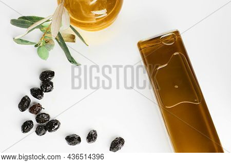 Extra Virgin Olive Oil In A Glass Bottles And Smoked Olives On White Background.