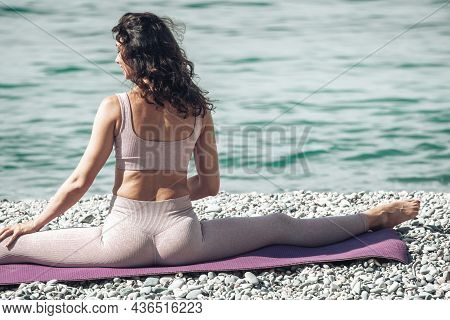 Young Woman With Black Hair, Fitness Instructor In Leggings And Tops Doing Stretching And Pilates On