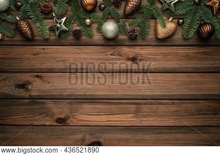 Holiday Christmas background with a frame made of decorated fir branches and sleigh bells