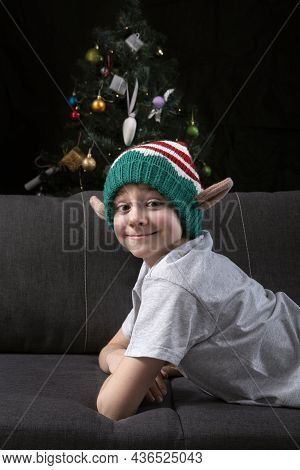Happy Smiling Cute Boy In Christmas Elf Hat Is Resting On The Sofa And Looks At Camera On The Backgr