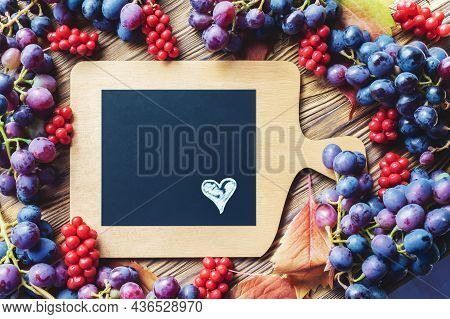 Bright Autumn Background Of Grapes And Lemongrass With A Copy Of The Space. Top View. Heart On A Bla