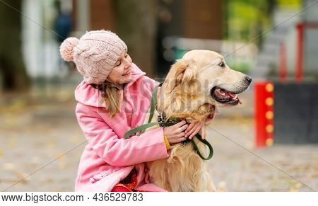 Preteen girl kid with golden retriever dog sitting in the park and hugging doggy. Female child with pet at autumn
