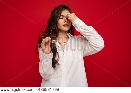 Shot Of Attractive Sorrowful Sad Upset Young Curly Brunette Woman Wearing White Shirt And Optical Gl