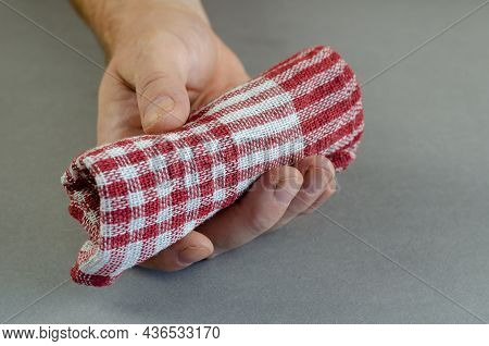 A Man Is Holding A Checkered Napkin. Red And White Cotton Kitchen Towel Rolled Up. Close-up. Selecti