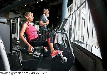 Beautiful Young Looking Senior Woman In Pink Top Cycling In Gym Together With Elder Bearded Man In G