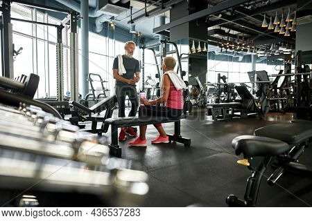 Sporty Aged Woman And Man Chatting After Working Out In Large Modern Gym With Variety Of Equipment.