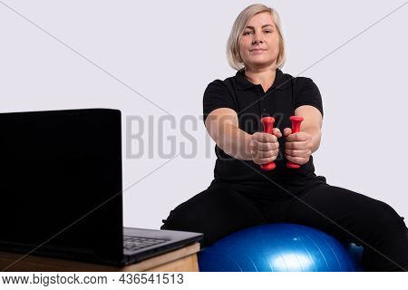 Sporty Healthy Lifestyle. Slender And Sporty Senior Woman In Sportswear Trains At Home In The Mornin