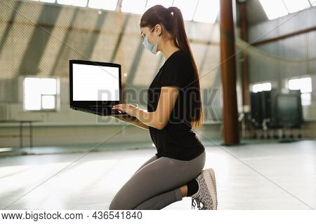 Fitness Trainer Kneel Down In Empty Gym. Woman In Medical Mask Works Remotely Indoor In Solitude. Sh