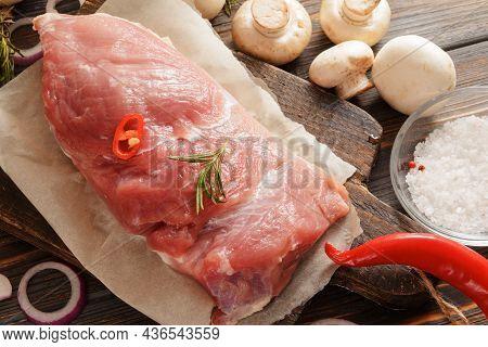 Raw Pork Tenderloin With Mushrooms,  Salt On A Dark Wooden Background