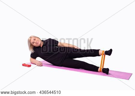 Pretty Elderly Woman In Sporty Outfit Exercising Leg Muscles, Using Elastic Band Resistance, Lying O