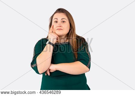 Photo Of Thoughtful Young Large Woman Standing Isolated Over A Gray Wall Background. Confident Overw