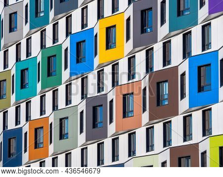 The Multi-colored Facade Of A High-rise Residential Building. Rows Of Windows