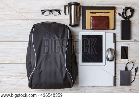Flat Lays Concepts. Top View Flat Lay Of Backpack With Laptop And Tablet Nearby, Mobile Phone With N