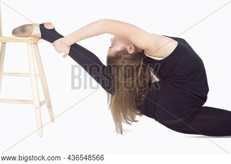 Athletic Caucasian Sportswoman Rhythmic Gymnast In Training Outfit During Legs Backward Stretching E