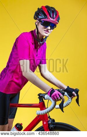 Cycling Sport Concepts. Young Positive Female Road Cyclist Posing With Modern Race Bike Against Yell