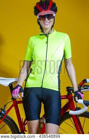 Cycling Sport Concepts. Professional Female  Road Cyclist Posing With Modern Race Bike Against Yello