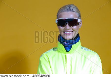Portrait Of Smiling Positive Female Road Cyclist In Professional Outfit Standing In Green Autumn Jac