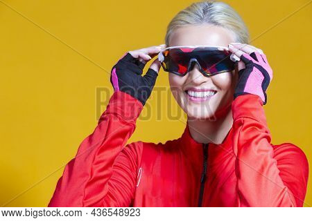 Cycling Ideas. Portrait Of Positive Female Road Cyclist In Professional Outfit Posing Against Yellow