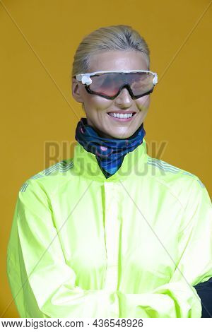 Female Road Cyclist In Professional Warm Outfit Standing In Green Autumn Jacket And Goggles With Sky