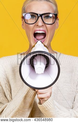 Portrait Of Caucasian Expressive Blond Woman Shouting At Megaphone Isolated On Yellow.