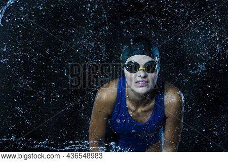 Watersports Concepts. Sportive Caucasian Female Swimmer In Swimsuit Posing In Goggles In Aqua Studio