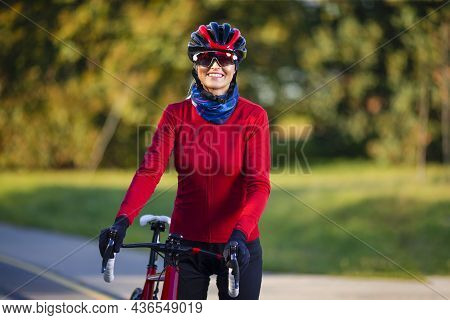 Road Cycling. Caucasian Female Cyclist With Road Bike Posing Outdoors Against Autumn Background. Hor