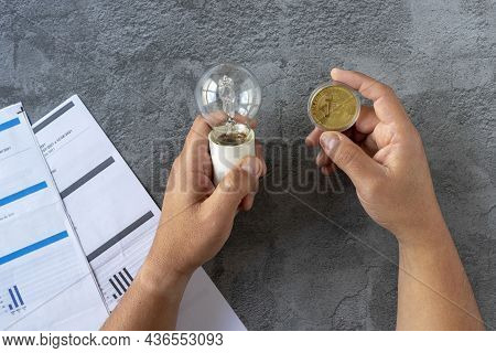 Electricity Costs: Person Checking Electricity Bills With A Light Bulb In One Hand And A Bitcoin In