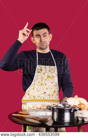Caucasian Brunette Hipster Chef-cook Pointing Forefinger Up. Male Chef In Uniform Thinking About The