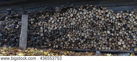 Neatly Stacked Big Pile Of Chopped Fire Wood Logs Prepared For Winter At Vintage Wooden Barn Wall. T