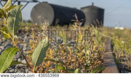 A Metal Fuel Tank In An Antique Railway Yard. Old Black Fuel Tank On The Village Railroad Station. I