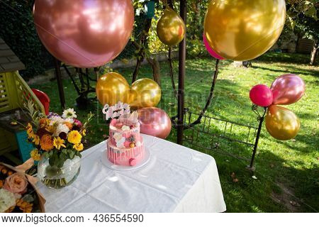 birthday garden party cake and balloons in back yard